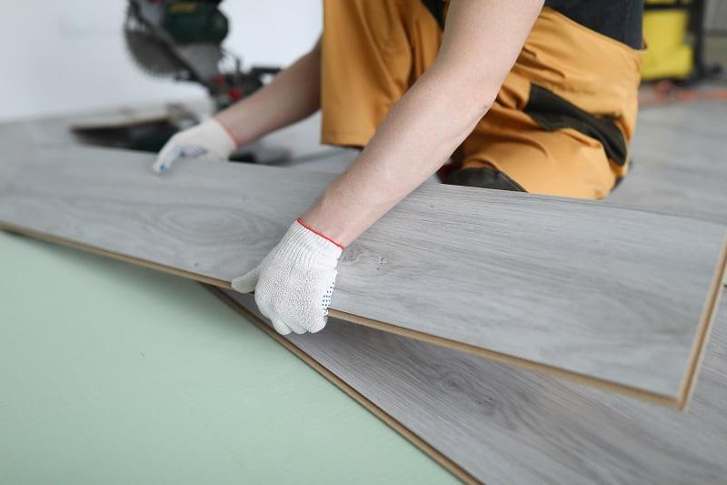 mężczyzna układa (kładzie) panele podłogowe